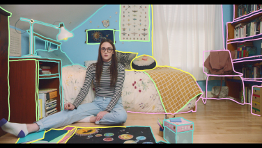 Still from the film: Violet, in front of a drawing of our galaxy, sitting up and paralyzed with terror. There are bright, hand-drawn outlines around the objects in her room.