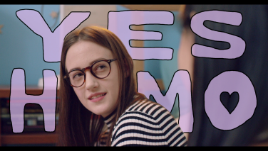 "Still from the film: Violet smiling towards camera, the words ""YES HOMO"" drawn and super-imposed behind her head."