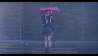 Still from the film: Violet drenched in the rain, cellphone to her ear, devastated.